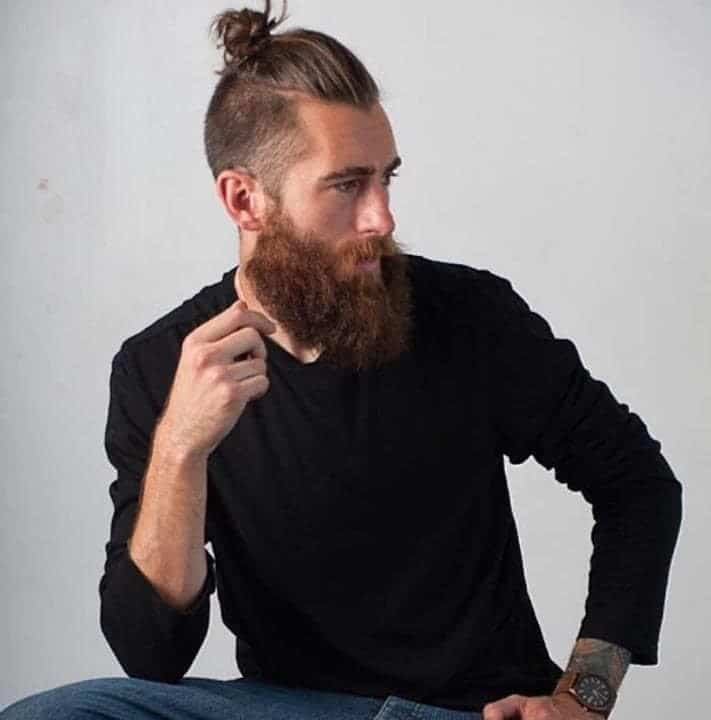 guy posing with a messy top knot bun