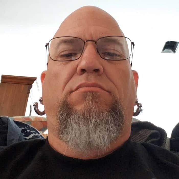 shaved head and scruffy beard