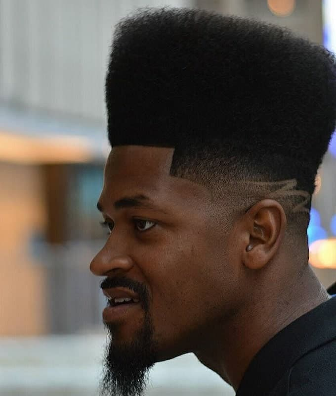 black guy with curly high top fade