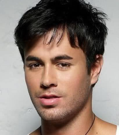 Image of Enrique Iglesias hairstyle with bangs.