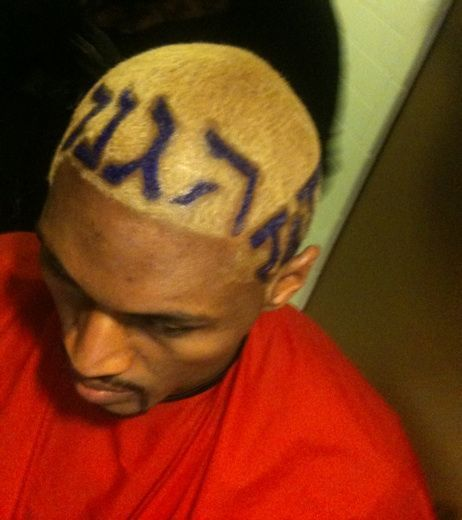 Photo of Ron Artest hairstyle with the letter Defense in Hebrew, Japanese, and Hindi.