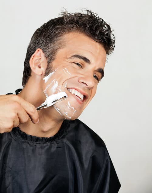 Photo of a man shaving his beard.