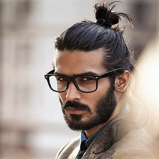Man with top knot staring